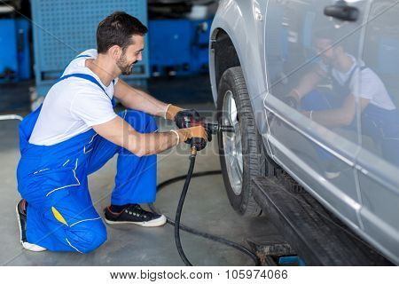 male mechanic repairing car wheel in workshop with wrench
