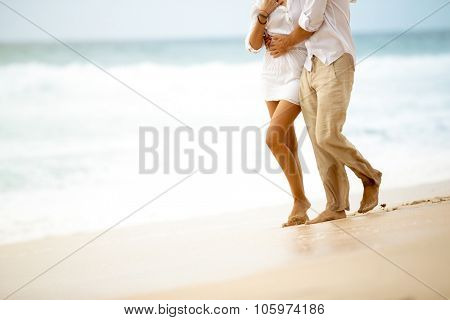 Barefoot couple in relaxing walk on beach