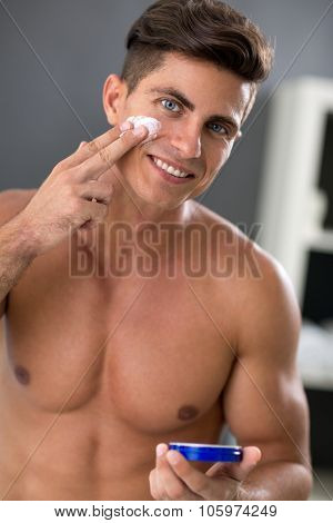 Young man putting on cream lotion on face in  bathroom