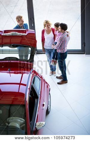 Salesman offering a car to family in the car dealership  saloon, overhead view