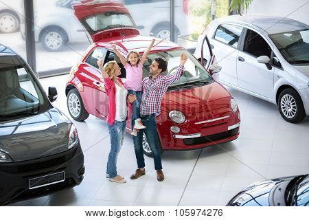 excited family buying a new car in the car dealership  saloon