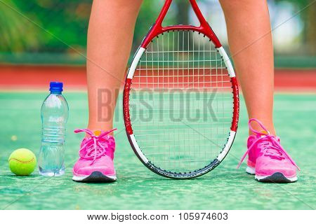 Closeup of shoes with the tennis racquet and ball outdoors