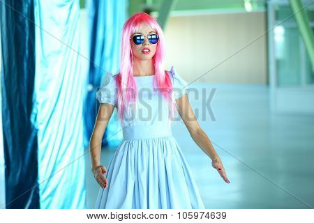 Young woman in mini dress posing like doll inside empty building
