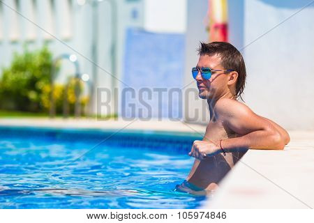 Young happy man relaxing in swimming pool outdoors