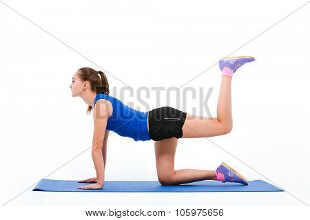 Young beautiful sportswoman in navy top and black shorts doing aerobic