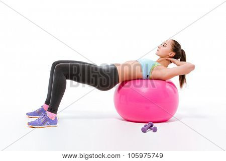 Portrait of a sports woman doing exercises on fitness ball isolated on a white background