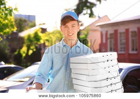 Pizza delivery boy holding boxes with pizza near car