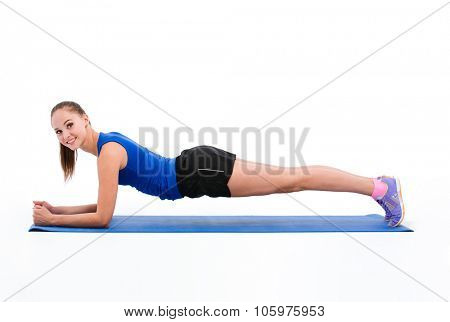 Young beautiful happy smiling sportswoman in navy top and black shorts doing pilates