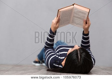 Young woman in striped jumper lying on the floor and reading a book