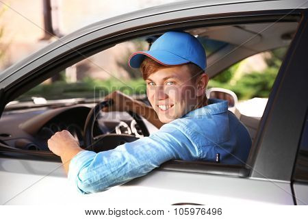 Pizza delivery boy with tablet in car, close-up
