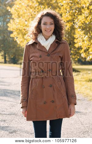 Beautiful young woman with curly hair posing outdoors in a coat at autumn