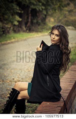 beautiful long hair young woman portrait in coat sit on brick wall on cobble path in park