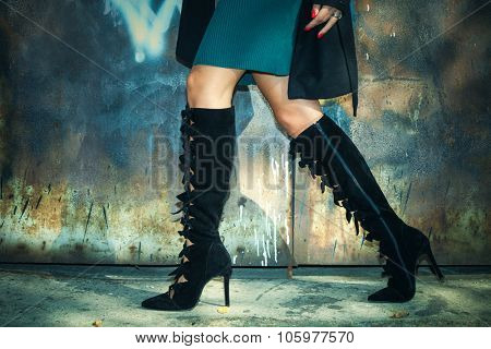 woman legs in black high heel boots  and short skirt outdoor shot against old metal door