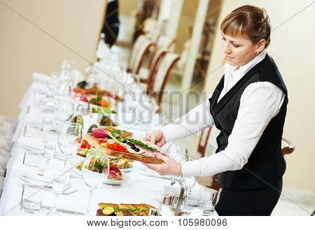 Restaurant catering services. Two female waitress serving banquet table