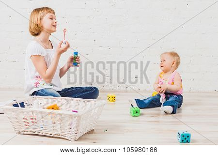 Beautiful girl blows bubbles to her little sibling