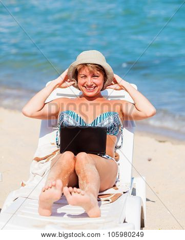 Smiling woman sitting on sunbed