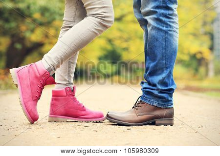 A picture of couple's legs in the park in autumn