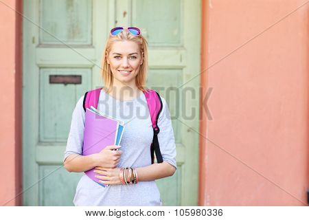A picture of a young female student standing at the campus