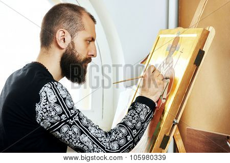 Iconography. Religious icon painter man paints a new icon with brush at workshop