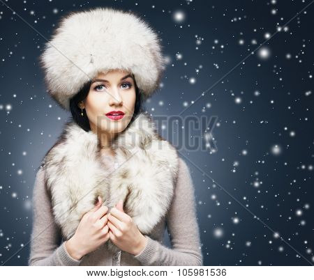 Portrait of a young and beautiful lady in a typical Russian winter clothes over snowy background.