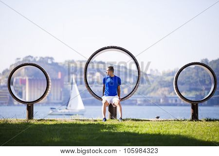 Man exercising with sit ups at Lisbon, next to the river