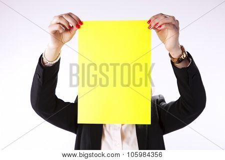 Businesswoman hidding her face behind a yellow paper