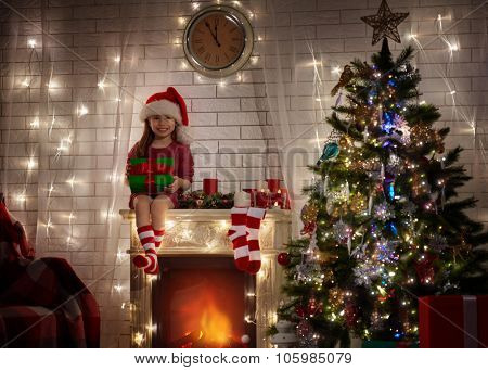 Little girl in Santa's hat sitting on the fireplace and holding a gift in hands