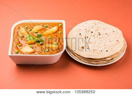 potato curry or aalu masala or aaloo masala with green peas, served with indian bread / roti / chapa