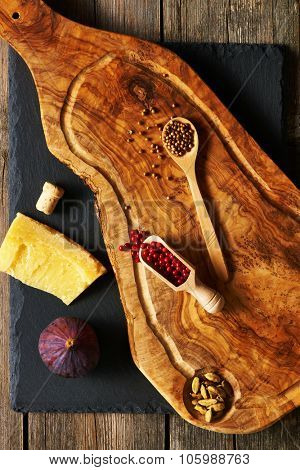 Olive wood cutting board with spices and fig over slate