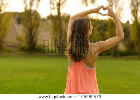Beautiful woman after the exercise making a hearth shape