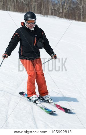 Young Woman Skier Coming Down The Ski From A Mountain On A Sunny Day