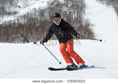 Young Woman Skier Coming Down The Ski From Mountain On A Sunny Day