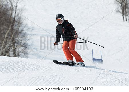 Young Woman Skier Coming Down The Ski From Mountain On Sunny Day