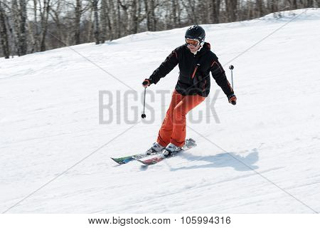 Young Woman Skier Coming Down The Slope On Sunny Day