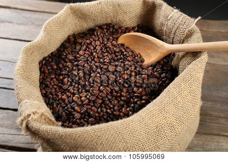 Sac with roasted coffee beans with spoon on wooden background