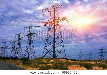 High-voltage Power Lines Against The Sky With The Sun