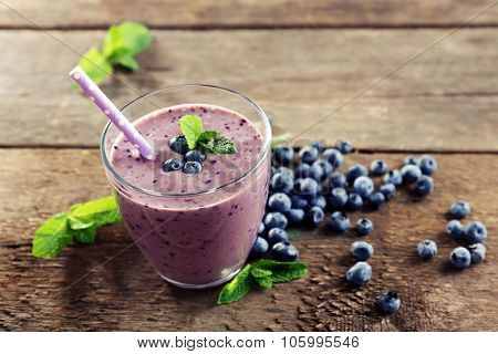 Tasty blueberry yogurt with berries and mint around on wooden background