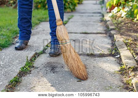 Woman Sweeps At Autumn