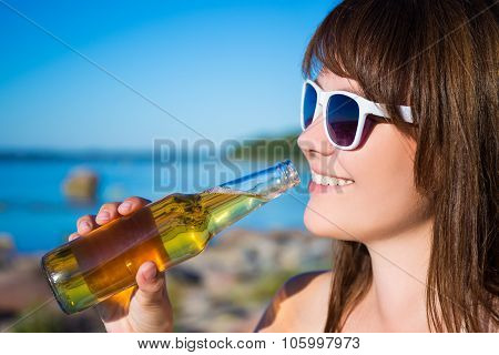 Portrait Of Beautiful Woman Drinking Beer On The Beach