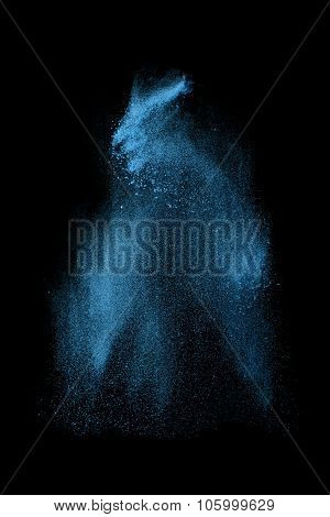 Abstract design of blue powder cloud against dark background
