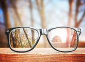 hipster glasses on a park bench or table with a forest in the background toned with a retro vintage poster