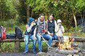 camping, travel, tourism, hike and people concept - happy family sitting on bench and drinking hot t poster