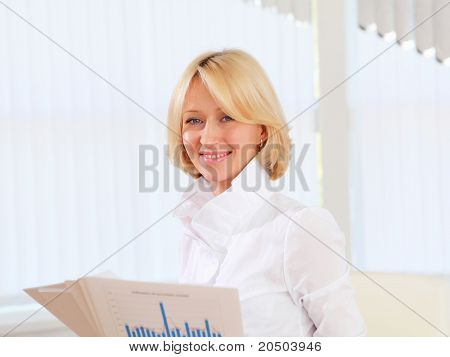 portrait of a young business woman with papers in the offcie
