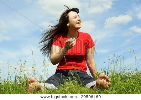 Young Barefooted Women Siting On Summer Meadow And Smiling, Blue Sky