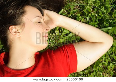 Closeup Of Young Brunette Girl Lying On Summer Meadow And Smiling, Closing Eyes