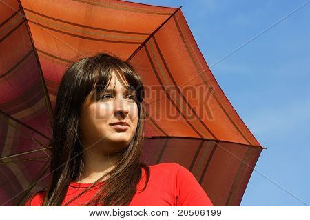 Young Brunette Girl Holding Red Umbrella, Blue Sky