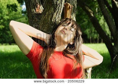 Young Brunette Girl In Red Shirt Siting Near Tree And Dreaming, Hands Beinnd Head, Eyed Closed