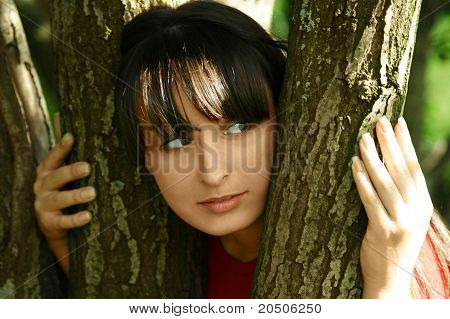 Young Beautiful Brunette Girl Looking Out Of Trees, Summer Time