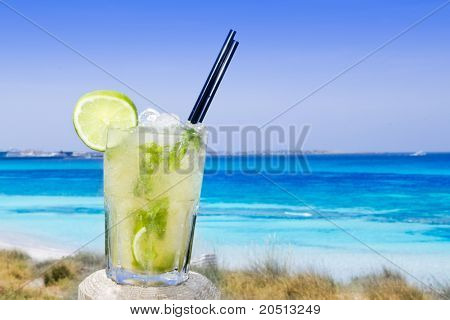 Cocktail mojito ice lemon straws in tropical beach balearic Islands