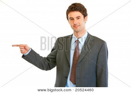 Smiling modern businessman pointing finger at copy space isolated on white